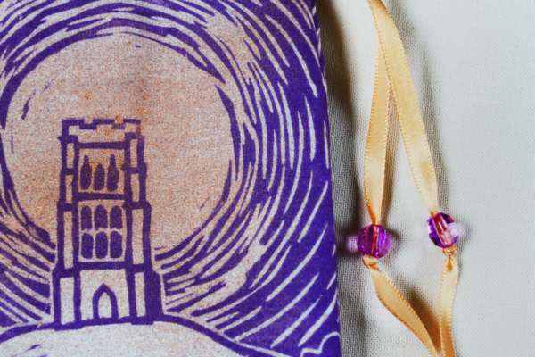 Glastonbury Tor Pouch, Mystical Avalon Tower on Hill with Glastonbury Spiral White Spring - Unbleached Cotton Pouch with Copper Spray and Purple Printing Close Up - Hand Printed with Hand Carved Lino Stamp
